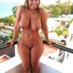 Epouse libertine plantureuse nue sur son balcon